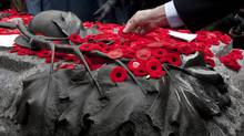 A man places his poppy on the Tomb of the Unknown Soldier following Remembrance Day ceremonies at the National War Memorial in Ottawa Friday November 11, 2011. (Adrian Wyld/Adrian Wyld/The Canadian Press)