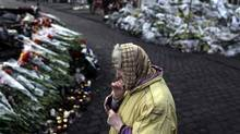 A woman stands in front of a memorial for the people killed in clashes with police at Kiev's Independence Square, the epicenter of the country's current unrest, Thursday, Feb. 27, 2014. Ukraine put its police on high alert after dozens of armed pro-Russia men stormed and seized local government buildings in Ukraine's Crimea region early Thursday and raised a Russian flag over a barricade. (Marko Drobnjakovic/Associated Press)