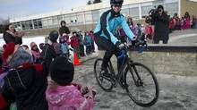 Clara Hughes rides her bike past students at an Oshawa, Ont., school on March 6, 2014. (Kevin Van Paassen/The Globe and Mail)