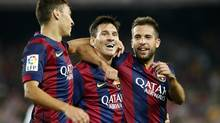 Barcelona's Lionel Messi, centre, celebrates his second goal with teammate Munir El Haddadi, left, and Jordi Alba during their Spanish first division soccer match against Elche at Nou Camp stadium in Barcelona, August 24, 2014. (GUSTAU NACARINO/REUTERS)