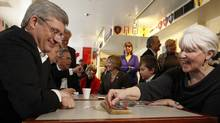 Conservative Leader Stephen Harper plays cribbage with Susan Collins during a campaign stop at a cultural centre in Toronto. (Chris Wattie/Reuters)
