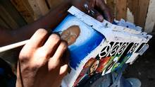 Artist Marius Yvon, part of Reginald Jean Francis's team at Slum-Toys-Project in partnership with the Brand Aid Project, paints a portrait on a Tap-Tap toy bus made from metal tins of all sort picked out of Haitian trash in Port Au Prince, Haiti. (Deborah Baic/Deborah Baic/The Globe and Mail)
