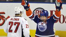 Edmonton Oilers' Shawn Horcoff (R) celebrates a goal against Washington Capitals' Karl Alzner during their NHL hockey game in Edmonton October 27, 2011. (DAN RIEDLHUBER/REUTERS)
