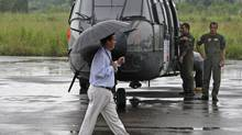 Colombian High Commissioner for Peace Frank Pearl walks past a helicopter, marked with the International Red Cross logo, at the airport in Florencia March 30, 2010. Mr. Pearl has worked hard to negotiate a peace agreement with the FARC. (© John Vizcaino / Reuters/REUTERS)