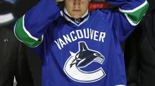 Bo Horvat tries on his Vancouver Canucks jersey and cap after being selected by the Canucks as the ninth overall pick in the 2013 National Hockey league (NHL) draft in Newark, New Jersey, June 30, 2013. (Brendan McDermid/Reuters)
