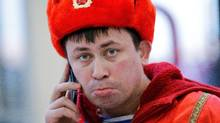 A Russia fan talks on his mobile phone as he leave the area after Russia's 3-1 loss to Finland (David J. Phillip/Associated Press)