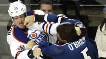Edmonton Oilers' Andy Sutton and Colorado Avalanche's Shane O'Brien fight during the third period of an NHL hockey game on Friday. (Barry Gutierrez/Associated Press)