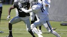 Oakland Raiders defensive back Chimdi Chekwa, left, and wide receiver Mike Davis, right, take part in a blocking drill during their NFL football training camp Sunday, July 27, 2014, in Napa, Calif. (Eric Risberg/AP)