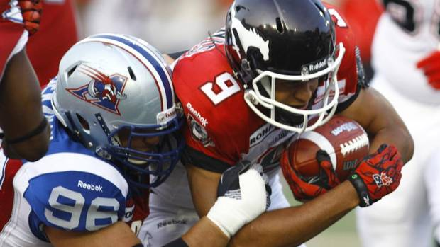 Calgary Stampeders Jon Cornish (9) is tackled by Montreal Alouettes J.P. Bekasiak (96) during the first half of their CFL game in Montreal July 12, 2012. (OLIVIER JEAN/REUTERS)