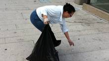 Vancouver resident Edna Bell picks up trash on Robson Street, the morning after a clash between rioters and police, Vancouver, June 16, 2011. (Sunny Dhillon/ The Globe and Mail/Sunny Dhillon/ The Globe and Mail)