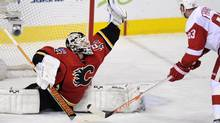 Calgary Flames goalie Miikka Kiprusoff, left, from Finland, makes a save during the closing seconds of the third period as Detroit Red Wings' Johan Franzen, from Sweden, looks for a rebound during NHL action in Calgary, Alberta, Wednesday, April 17, 2013. (Larry MacDougal/THE CANADIAN PRESS)