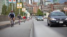 Cyclists make their way over the Burrard Bridge bike lane in Vancouver. (Brett Beadle For The Globe and Mail)