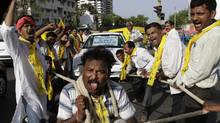 Consumers in Ahmadabad, India pull a car by rope on May 24 to protest gasoline prices. Opposition parties are calling for a national strike on Thursday. (Ajit Solanki/AJIT SOLANKI/AP)
