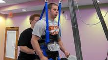 A photo released on May 19, 2011 shows Rob Summers, a paraplegic being moved into position on a treadmill where he has been able to stand and take repeated steps voluntarily following epidural spinal cord stimulation and repeated motion training. (AFP/Getty Images)