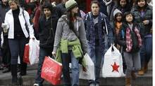 Shoppers carry their bags as they walk in downtown Seattle on Friday, Nov. 26, 2010. (Ted S. Warren/AP/Ted S. Warren/AP)