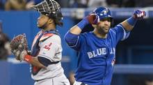 Toronto Blue Jays Jose Bautista celebrates in front of Cleveland Indians catcher Carlos Santana after hitting a two run homer during first inning AL baseball action in Toronto on Thursday, April 4, 2013. (Chris Young/THE CANADIAN PRESS)