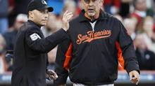 Home plate umpire Dan Lassogna points to the bull pen as San Francisco Giants manager Bruce Bochy (R) brings in pitcher Tim Lincecum in the fourth inning against the Cincinnati Reds during Game 4 of their MLB NLDS playoff baseball series in Cincinnati, Ohio October 10, 2012. (JEFF HAYNES/REUTERS)