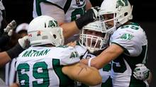 Saskatchewan Roughriders' Corey Watman, from left to right, Dan Clark and Chris Getzlaf celebrate Clark's touchdown against the B.C. Lions during the second half of a CFL football game in Vancouver, B.C., on Sunday August 24, 2014. (DARRYL DYCK/THE CANADIAN PRESS)
