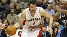 Toronto Raptors centre Andrea Bargnani drives on Dallas Mavericks forward Lamar Odom during the second half of their NBA basketball game in Dallas, Texas December 30, 2011. (Reuters)