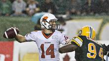 B.C. Lions quarterback Travis Lulay (14) looks for the pass as he is chased by Edmonton Eskimos' Ted Laurent (94) during first half action in Edmonton, Alta., on Saturday July 13, 2013. (JASON FRANSON/THE CANADIAN PRESS)