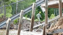 A Hydro Quebec worker navigates a causeway where a section of road collapsed following an earthquake in Bowman, Quebec Wednesday June 23, 2010. (Adrian Wyld/Adrian Wyld/THE CANADIAN PRESS)