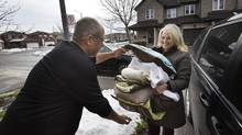 Sponsor Sandra Onufryk brings some linens and bedding for Riad Al Blkihi as his family settles into their new home in Mississauga, Ont. on Jan 8 2016. (Fred Lum/The Globe and Mail)