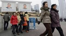 People walk near giant portraits of late North Korean leaders, Kim Il Sung, left, and his son Kim Jong Il, in Pyongyang, North Korea, Tuesday, Jan. 29, 2013. (AP)