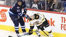 Jets defenseman Dustin Byfuglien battles David Pastrnak during the second period at the MTS Centre. (Bruce Fedyck/USA Today Sports)