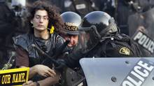 In this June 27, 2010 file photo, a protester with a daisy clenched in his teeth is seized by riot police during protests at the G8 and G20 Summits in Toronto. (Carolyn Kaster/AP/Carolyn Kaster/AP)