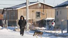 A man walks down the street in Attawapiskat, Ont., Tuesday November 29, 2011. (Adrian Wyld/THE CANADIAN PRESS)