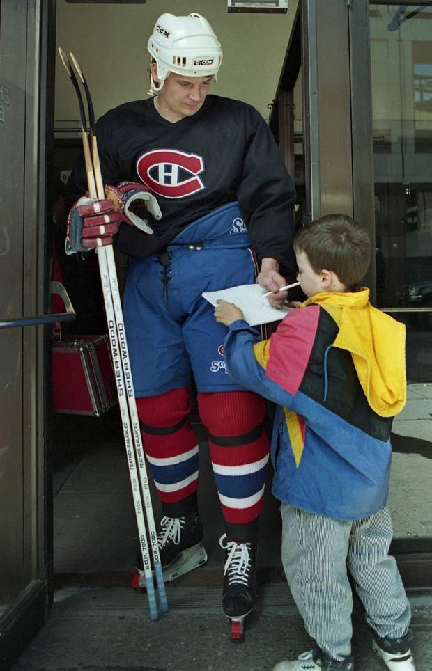 Montreal Canadiens forward Todd Ewen signs an autograph for a young fan at the Forum in Montreal on May 27, 1993.