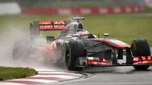McLaren Mercedes driver Jenson Button navigates through a puddle during the morning practice session at the Canadian Grand Prix in Montreal on Friday. (Graham Hughes/THE CANADIAN PRESS)