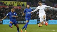 Two Leicester defenders vie for the ball with Swansea's Tom Carroll, right, on Sunday at Liberty Stadium in Wales. (Paul Childs/REUTERS)