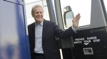 Quebec Premier Jean Charest smiles as he boards his campaign bus following an election stop at the Jefo manufacturing plant in Saint Hyacinthe, Que., Thursday, August 2, 2012. (Graham Hughes/THE CANADIAN PRESS)