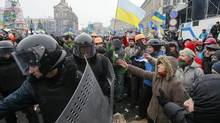Interior Ministry personnel leave Independence Square as pro-European integration protesters gesture in central Kiev December 11, 2013. (GLEB GARANICH/REUTERS)