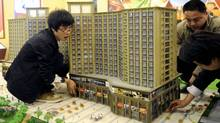 Workers adjust a building model as they prepare for the 2011 Spring Real Estate Fair in Nanjing, Jiangsu province on April 20, 2011. (CHINA DAILY/Reuters/China Daily)