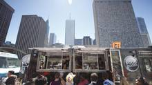 People line up at the Food Dudes truck in Toronto's Nathan Phillips Square. A pilot program will bring trucks into five city parks starting Aug. 1. (Gloria Nieto/The Globe and Mail)