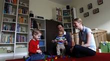 Ten-month-old Leonard Rixom plays with his brother Benjamin, 2, and his parents Veronika and Barry in their living-room in Ismaning near Munich, November 8, 2012. (Michaela Rehle/REUTERS)