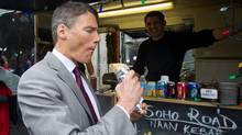 Vancouver Mayor Gregor Robertson takes a bite of a vegetarian naan wrap prepared by Sarb Mund at his Soho Road food truck outside Vancouver City Hall. (DARRYL DYCK/Darryl Dyck for The Globe and Mail)