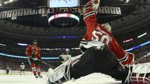 Chicago Blackhawks goalie Corey Crawford (50) makes a glove save against the Boston Bruins during Game 1 of their NHL Stanley Cup Finals series in Chicago, Illinois, June 12, 2013. (POOL/REUTERS)