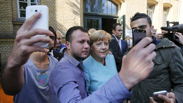 Migrants from Syria and Iraq take selfies with Ms. Merkel after their registration in Berlin on Sept. 10, 2015. Anti-immigrant populism could play a key role in deciding Germany's election, as it has in several other European countries recently.