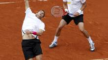Max Mirnyi of Belarus (L) and Daniel Nestor of Canada return the ball to Bob Bryan and his brother Mike Bryan of the U.S. during their men's doubles final at the French Open tennis tournament at the Roland Garros stadium in Paris June 9, 2012. (FRANCOIS LENOIR/REUTERS)
