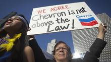 A protester holds up a sign as he demonstrates against Chevron's Racketeer Influenced and Corrupt Organizations (RICO) trial in New York, October 15, 2013. (CARLO ALLEGRI/REUTERS)