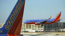 In this Feb. 9, 2012, a Southwest Airlines Boeing lands at Chicago's Midway Airport as another sits at a gate. Southwest Airlines Co. said Thursday, March 1, 2012, that it took a step toward combining its fleet with that of AirTran Airways as U.S. officials gave the airlines a single operating certificate.(AP Photo/Charles Rex Arbogast) (Charles Rex Arbogast/AP)