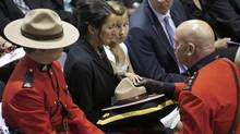 Angela, the widow of Constable Fabrice Georges Gevaudan, accepts her husband's Stetson and flag as his stepdaughter Emma looks on. (MARK BLINCH/REUTERS)