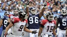 Toronto Argonauts defensive end Ricky Foley (96) celebrates after recovering a fumble as Calgary Stampeders running back Jon Cornish (9) and quarterback Kevin Glenn (15) walk to the sideline during the first half of their CFL game in Toronto July 7, 2012. (MIKE CASSESE/REUTERS)