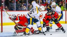 Calgary Flames goalie Karri Ramo guards his net as Nashville Predators centre Cody Bass and Calgary Flames defenceman Dennis Wideman battle for the puck during the first period at Scotiabank Saddledome. (Sergei Belski/USA Today Sports)