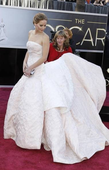 Jennifer Lawrence waits while an assistant passes a bottle of water to the homeless person hired to fill out the back half of her couture gown. (Lucas Jackson/Reuters)
