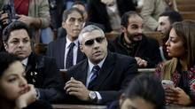 Canadian Al-Jazeera English journalist Mohamed Fahmy, center, attends his retrial at a court in Cairo, Egypt, Monday, Feb. 23, 2015. The retrial of two Al-Jazeera English journalists who face terror-related charges in a case widely criticized by human rights organizations and media groups has been postponed to March 8. (Amr Nabil/AP)