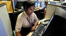 Employees at a call center provide service support to international customers, in the southern city of Bangalore March 17, 2004. (SHERWIN CRASTO/REUTERS)